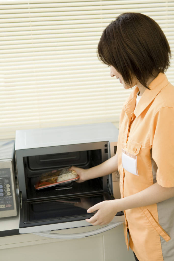 Salesclerk of convenience store putting boxed lunch into microwave
