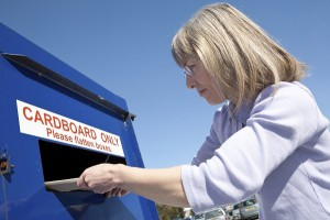 Woman inserting used cardboard packaging into a cardboard recycling bin.